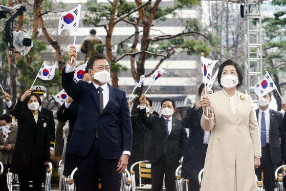 President Moon Jae-in, left, and first lady Kim Jung-sook wave the Taegeukgi (Korean national flag) in a ceremony marking the 102nd anniversary of the March 1 Independence Movement Day ceremony at Tapgol Park in Jongno District, central Seoul, Monday. [NEWS1]