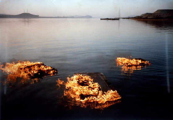 """""""Burning Canvases Floating on the River,"""" first performed in 1964 and recreated in this 1988 photo by Lee Seung-taek, the pioneer of Korean avant-garde art. The photo is included in the book ″Korean Art from 1953: Collision, Innovation, Interaction″ and is also on view now at the MMCA Seoul as part of Lee's retrospective .[MMCA]"""