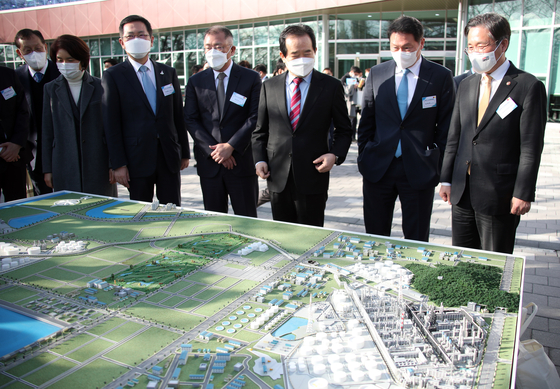 Prime Minister Chung Sye-kyun, third from right, looks at a model of a hydrogen plant at the factory of SK Incheon Petrochem on Tuesday, with SK Chairman Chey Tae-won, second from right, and Hyundai Motor Chairman Euisun Chung, fourth from right.