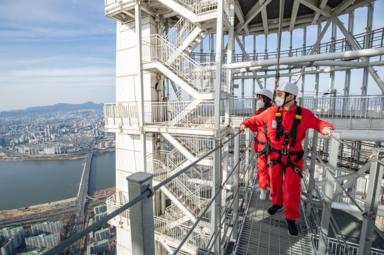 Models look at city below from Lotte World Tower's sky bridge in Seoul. According to Lotte, starting March 5, it will reopen its sky bridge tour, which was closed for the winter. The sky bridge tour program kicked off in July last year. [YONHAP]