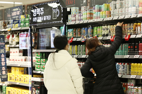 Customers pick beer off a shelf at Emart in Yongsan, Seoul on Tuesday. Beer sales at discount marts surged as lives have been restricted due to Covid-19 social distancing regulations. According to Emart, beer sales last year has jumped 150 percent. In January, they were up 230 percent. [YONHAP]