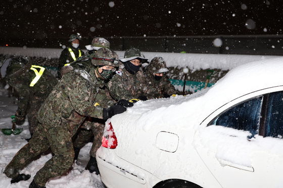 Soldiers from the 8th Army Corps and 102nd Armored Brigade push a car stuck on the road during a snowstorm Monday in Sokcho, Gangwon. [NEWS1]