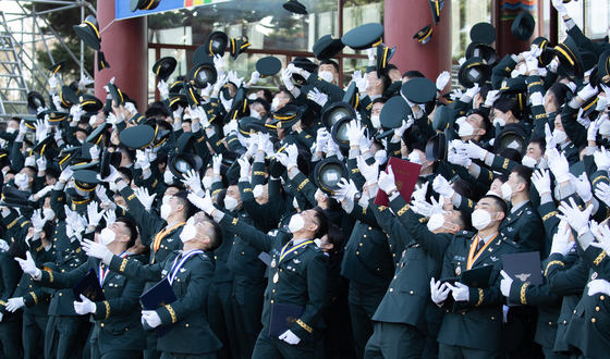 Cadets celebrate their graduation and toss their hats during the commission ceremony at the Korea Military Academy in Nowon District, northern Seoul, Tuesday. [NEWS1]