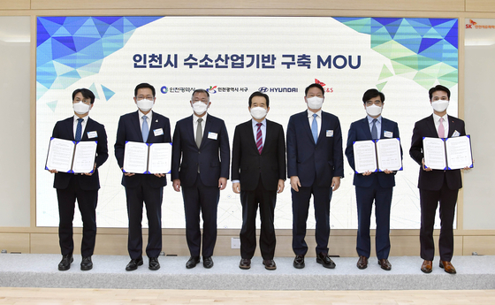 Korean Prime Minister Chung Sye-kyun, center, Hyundai Motor Group Chairman Euisun Chung, third from left, and SK Group Chairman Chey Tae-won, fifth from left, pose for a photo after signing a partnership to cooperate on hydrogen-related business in Incheon on Tuesday. [HYUNDAI MOTOR GROUP]