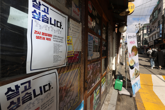 A poster for a restaurant in Seoul says it is difficult for small businesses to survive due to social distancing measures in place because of Covid-19, on Tuesday. [YONHAP]
