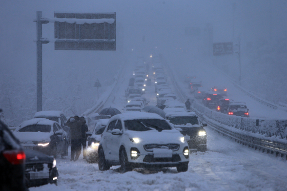 Cars are stuck on the road at Misiryeong Valley in Gangwon amid heavy snowfall Monday, the last day of a three-day weekend. [YONHAP]