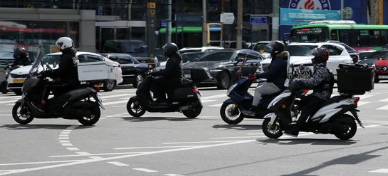 Delivery riders on a street in Seoul on Tuesday. [NEWS1]
