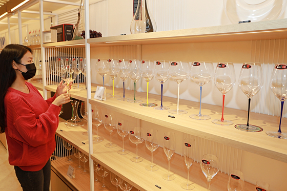A customer takes a look at Riedel wine glasses at Lotte Department Store's main branch in Myeong-dong, central Seoul on Tuesday. Austria's high-end wine glass brand Riedel opened its first Korean exclusive store at Lotte Department Store. [LOTTE SHOPPING]