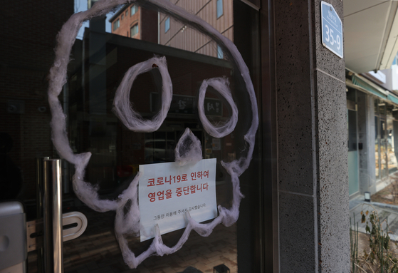 A store in Myeong-dong, central Seoul, is seen Wednesday with a notice saying it is closing due to Covid-19. The pandemic has devastated many small businesses especially in the services sector. [YONHAP]