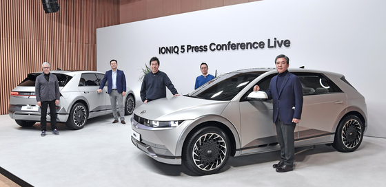 Chang Jae-hoon, CEO and President of Hyundai Motor, far right, and Lee Sang-yup, senior vice president and head of design, third from right, pose with the Ioniq 5 at an online press conference held Tuesday. [HYUNDAI MOTOR]