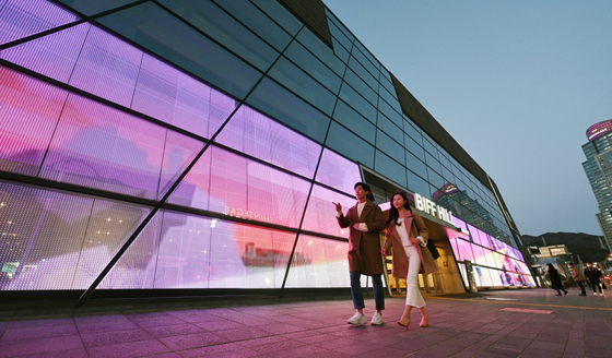 Models walk in front of the Busan Cinema Center in Busan on Wednesday. LG Electronics installed transparent LED film on the glass walls of the center as form of media art. [YONHAP]