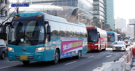 Chartered bus drivers from nationwide head toward Yeouido in western Seoul on Feb. 18 to call on the government to include them in its Covid-19 stimulus package. [NEWS1]