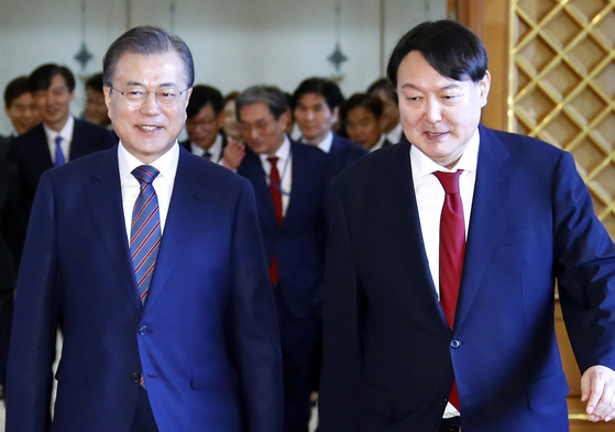 In this file photo, President Moon Jae-in, left, and Prosecutor General Yoon Seok-youl head toward a reception after Moon formally appoints Yoon as the top prosecutor on July 25, 2019.  [YONHAP]