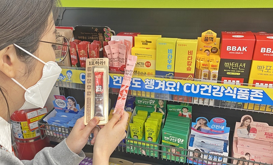 A woman shops for health supplements packaged in sachets at a CU. [BGF RETAIL]