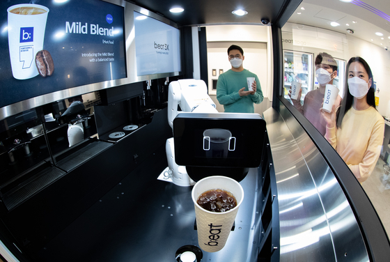 A robot barista used in a branch of B;eat coffee holds a cup of coffee in Bundang, Gyeonggi last Wednesday. [NEWS1]