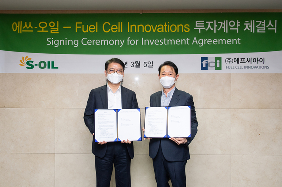 S-Oil President Ryu Yeol, left, and FCI representative director Lee Tae-won after the two companies forged a partnership at S-Oil headquarter in Mopo District, western Seoul, on Friday. [S-OIL]