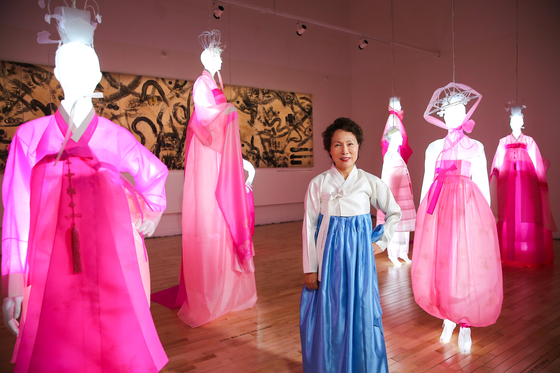 Hanbok designer Kim Hye-soon poses next to mannequins lit up with LED lights and wearing her hanbok at Kim Byung Jong Art Museum in Namwon, North Jeolla. [JANG JUNG-PIL]