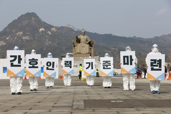The Korean Health Workers' Union calls for an increase in the number of nurses assigned to Covid-19 treatment wards and for better treatment of medical personnel in a rally in Gwanghwamun Square, central Seoul, Sunday. [YONHAP]
