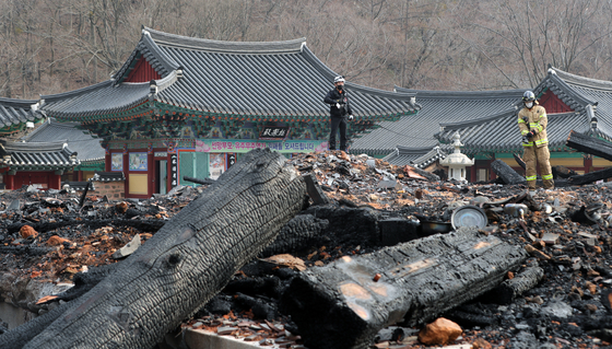 Firefighters on Saturday survey the charred remains of Daeungjeon hall at Naejang Temple in Jeongeup, North Jeolla after a disgruntled monk torched the building. [NEWS1]