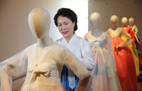 """Hanbok, or traditional Korean dress, designer Kim Hye-soon checking on mannequins wearing her work. Her hanbok is on display in the exhibit """"Dialogue"""" at Kim Byung Jong Art Museum in Namwon, North Jeolla, until May 9. [JANG JUNG-PIL]"""