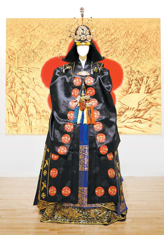 Traditional Korean garments for a queen from Joseon Dynasty (1392-1910) featured in front of artwork by Kim Byung-jong at Kim Byung Jong Art Museum. [JANG JUNG-PIL]