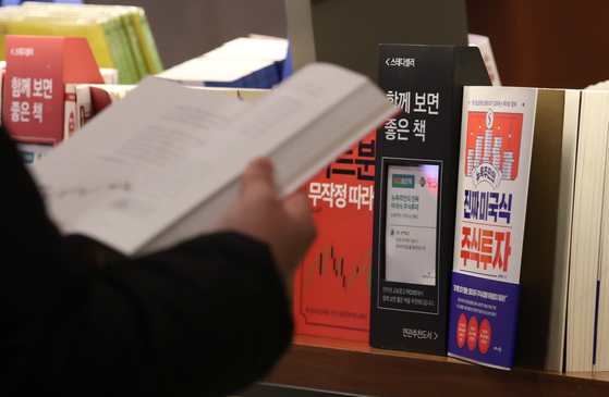 A customer looks at books on stock investment at a book store in central Seoul on Jan. 19. Stock investment interest has risen thanks to the bullish market. [YONHAP]