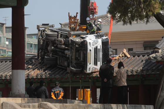 Workers prepare to lift a ladder truck that fell on the roof of the Dongsam Gate of the Confucian Shrine in Sungkyunkwan University in Jongno District, central Seoul, on Monday. The gate is Korea's Treasure No. 141. A crane truck dropped the ladder truck, which was supposed to prune branches of Natural Monument No. 59, a gingko tree at the shrine. [YONHAP]
