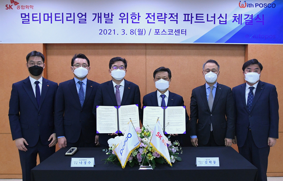 SK Global Chemical President Na Kyung-soo, third from left, and Posco President Kim Hag-dong, pose after signing a memorandum of understanding to jointly develop a new material for electric cars at Posco Center in Daechin-dong, southern Seoul, on Monday. [SK GLOBAL CHEMICAL]