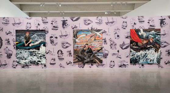 """Large-scale paintings by American artist Hernan Bas including """"The Young Man and the Sea,"""" left, are hanging on a wall covered with wallpaper, which is the artist's work """"Monsters and Mariners."""" They are part of a solo show of Bas, which started last month at Space K Seoul, a new museum that Kolon Group opened last autumn in Magok, a far western area of Seoul. [MOON SO-YOUNG]"""
