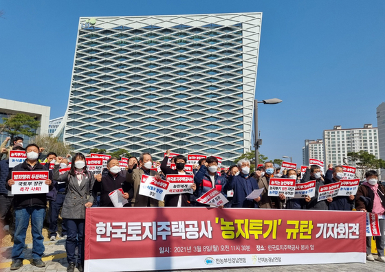Members of the National Farmers' League protest purchases by LH employees of agricultural land outside of the company's headquarters in Jinju, South Gyeongsang on Monday. [YONHAP]