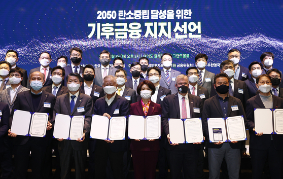 Top government officials including Environment Minister Han Jeoung-ae, center, and Financial Services Commission Chairman Eun Sung-soo and leading officials in the financial industry hold up a declaration promising to work toward carbon neutrality during an event held at Glad Hotel in Yeouido, Seoul, on Tuesday. Korea is targeting at carbon neutrality by 2050. [YONHAP]