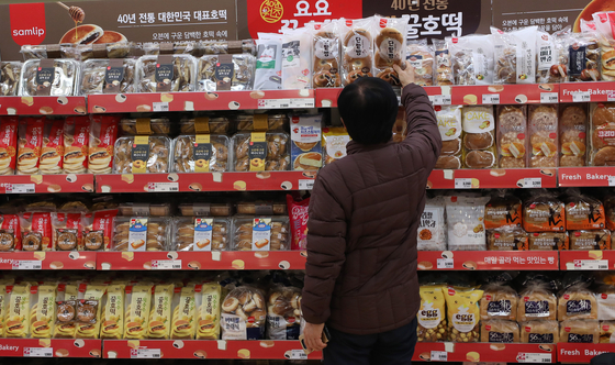 A customer looks at sweet bread on a shelf at a big discount store in downtown Seoul on Wednesday. With the price of grain sharply increasing across the globe, SPC Samlip said it will increase the prices of some 20 bakery products by around 9 percent starting from Friday. [NEWS1]