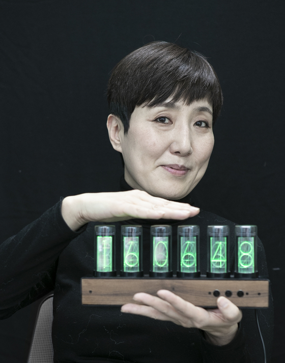 Choi Jung-yun, the founder of 11018 who put together the SBS music documentary series ″The Stage of Legends - Archive K,″ poses for photos during an interview held with the JoongAng Ilbo, an affiliate of the Korea JoongAng Daily in her office in eastern Seoul. She is holding a clock to symbolize her work on archiving history. [KWON HYUK-JAE]