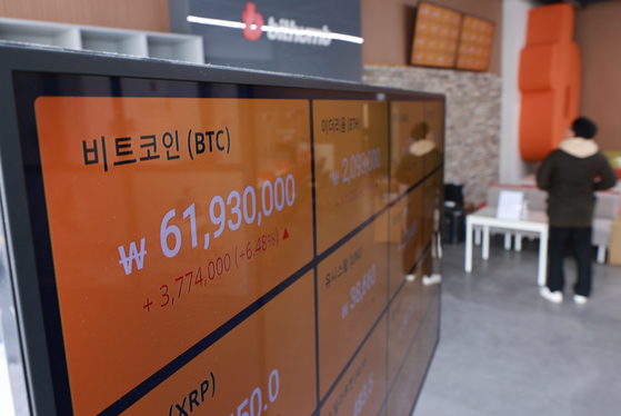 An electronic signboard at Bithum's Gangnam center shows the value of bitcoin trading above 61 million won ($53,500), which is a new record, on Tuesday. While the Kospi has fallen below the 3,000 mark, investors have been flocking to the virtual currency. [YONHAP]