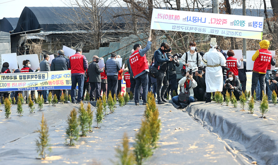Protesters on Wednesday demand the scrapping of a Gwangmyeong-Siheung development plan in front of a property allegedly bought by an LH employee based on inside information. [YONHAP]