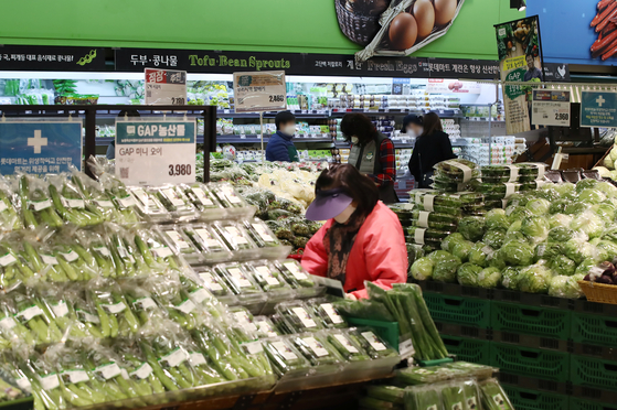 A shopper looks at vegetable at a discount store in Seoul on March 8. There has been growing worries over rising prices especially of food. [YONHAP]