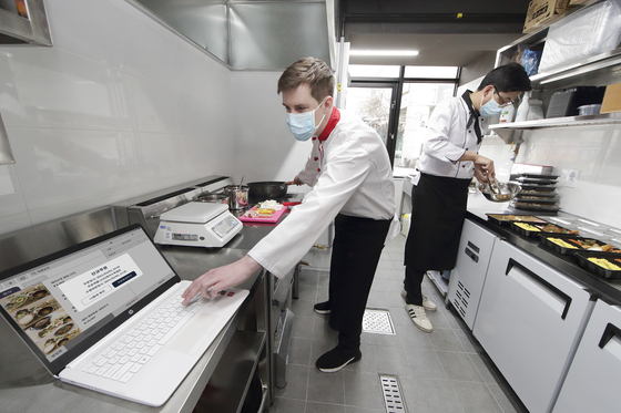 """Employees at 5km Kitchen in Seodaemun District, western Seoul, use KT's """"smart green kitchen"""" feature, Thursday. 5km Kitchen is a shared kitchen for small food delivery businesses that can accommodate up to 31 operators. Under an agreement with its operator, Kimchi Korea, KT will provide a digital solution for the shared kitchen. According to the mobile carrier, this system provides a wide range of features, including payments, monitoring air quality inside the kitchen, energy consumption and quarantine activities of deliverymen that enter the venue. [KT]"""
