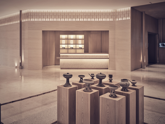 An exposed exhibit displaying Silla artifacts and earthenware welcomes guests at the center of the museum's lobby. [TEO YANG STUDIO]