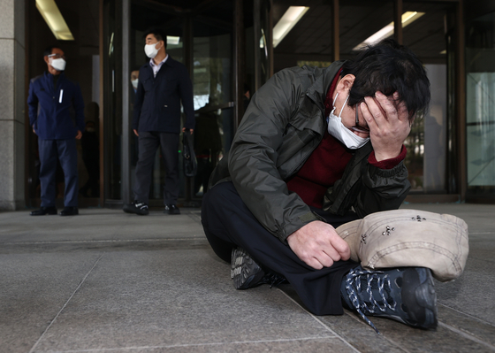A former inmate of Brothers Home slumps on the floor outside the Supreme Court in Seoul on Thursday and cries upon the dismissal of an appeal filed against a not-guilty verdict for Park In-keun, the owner of Brothers Home, the state-run homeless facility. [YONHAP]