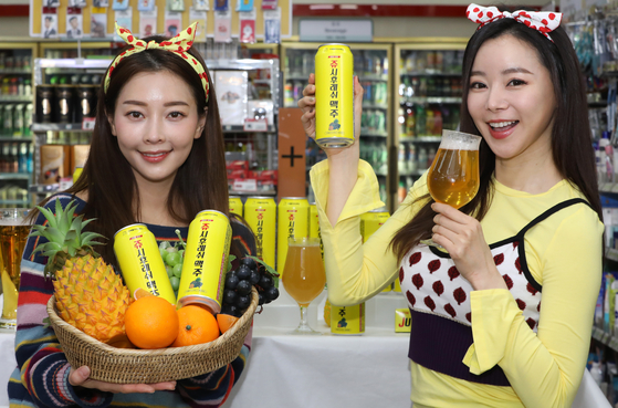 Models pose with Juicy & Fresh Beers that 7-Eleven launched in a collaboration with Lotte Confectionery's gum brand Juicy & Fresh in the convenience store's Sogong-dong branch in Jung District, central Seoul on Wednesday. [NEWS1]
