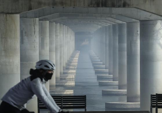 A cyclist rides on a bank of the Han River in Yeouido, western Seoul, on Thursday, as a thick blanket of fine dust air pollution descended on most of the country. The first emergency measures this year to reduce fine dust in the greater Seoul area were issued on Thursday.   [KIM SEONG-RYONG]