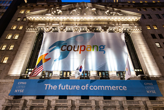 Flags raised ahead of Coupang's initial public offering in front of the New York Stock Exchange building on Thursday. [JOONGANG ILBO]