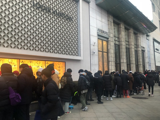 People lined up outside a department store waiting for a sale to begin. [LOTTE SHOPPING]