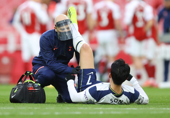 Tottenham Hotspur's Son Heung-min receives medical attention after sustaining an injury against Arsenal at Emirates Stadium in London on Sunday. [REUTERS/YONHAP]