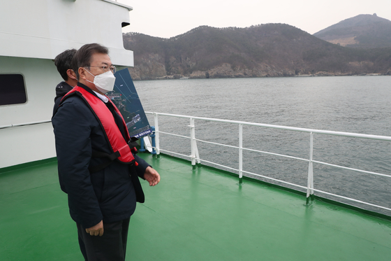 In this file photo from Feb. 25, President Moon Jae-in looks at Gadeok Island, the site of a new airport near Busan.  [YONHAP]
