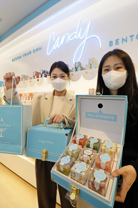 Models holding up candy from popular U.S. candy store Sugarfina at Galleria Department Store in Gangnam, Seoul, on Tuesday. Korea is the second place in Asia to get a Sugarfina store, after Hong Kong. [YONHAP]
