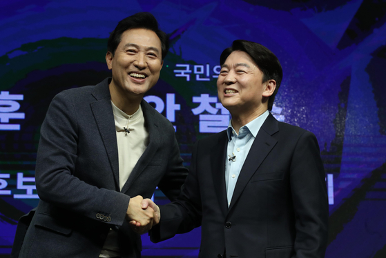 Seoul mayoral candidates Oh Se-hoon, left, of the People Power Party and Ahn Cheol-soo of the People's Party shake hands after announcing their visions for the opposition parties' plan to field a consolidated candidate in the April 7 Seoul mayoral by-election on Monday. [YONHAP]