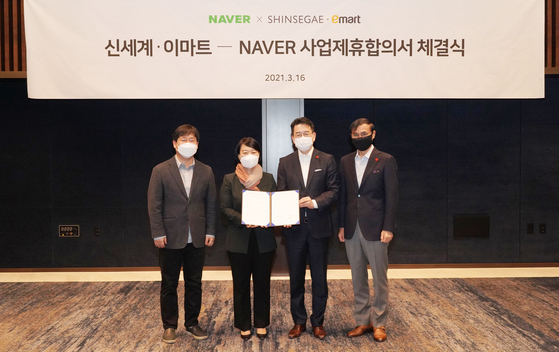 Representatives of Naver and Shinsegae celebrate a stock swap on Tuesday in southern Seoul. [YONHAP]