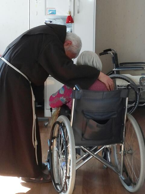 Father Uribe speaking with a patient at Sungsimwon in 2018. [SUNGSIMWON]