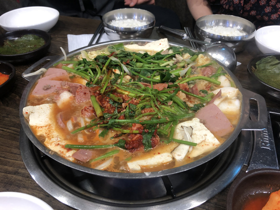 Daewoo Sikdang of Gangnam District, southern Seoul, serves minari on top of its budae jjigae, a stew boiled with various processed meat. [LEE SUN-MIN]